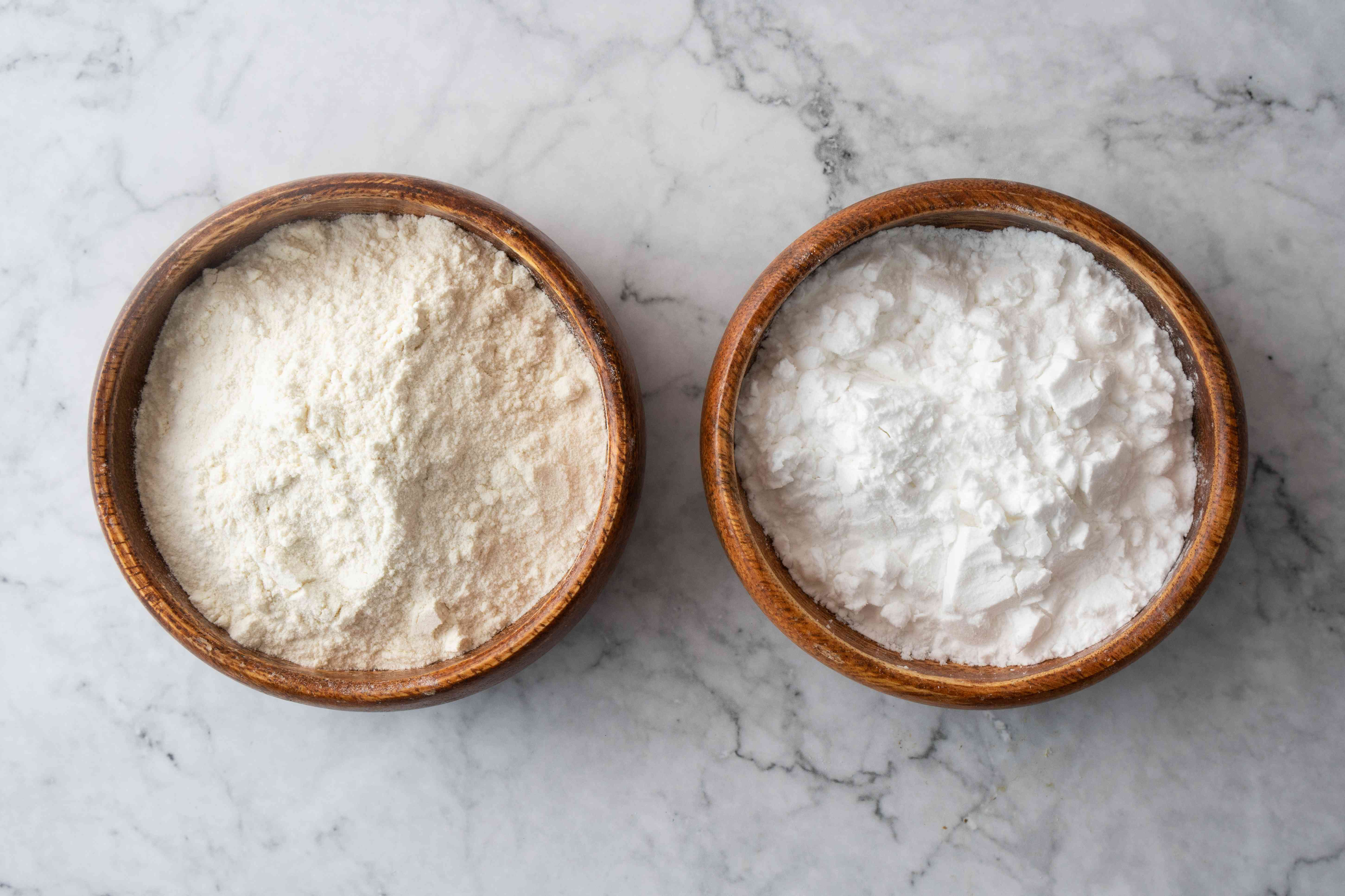 rice flour and corn starch in wooden bowls on white marble background