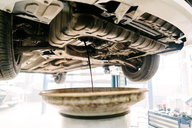 Engine oil drain unit. Car on a lift in a car service.