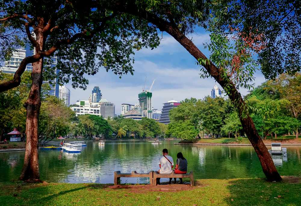 View of lake and shade trees in Lumphini Park with city of Bangkok in the distance