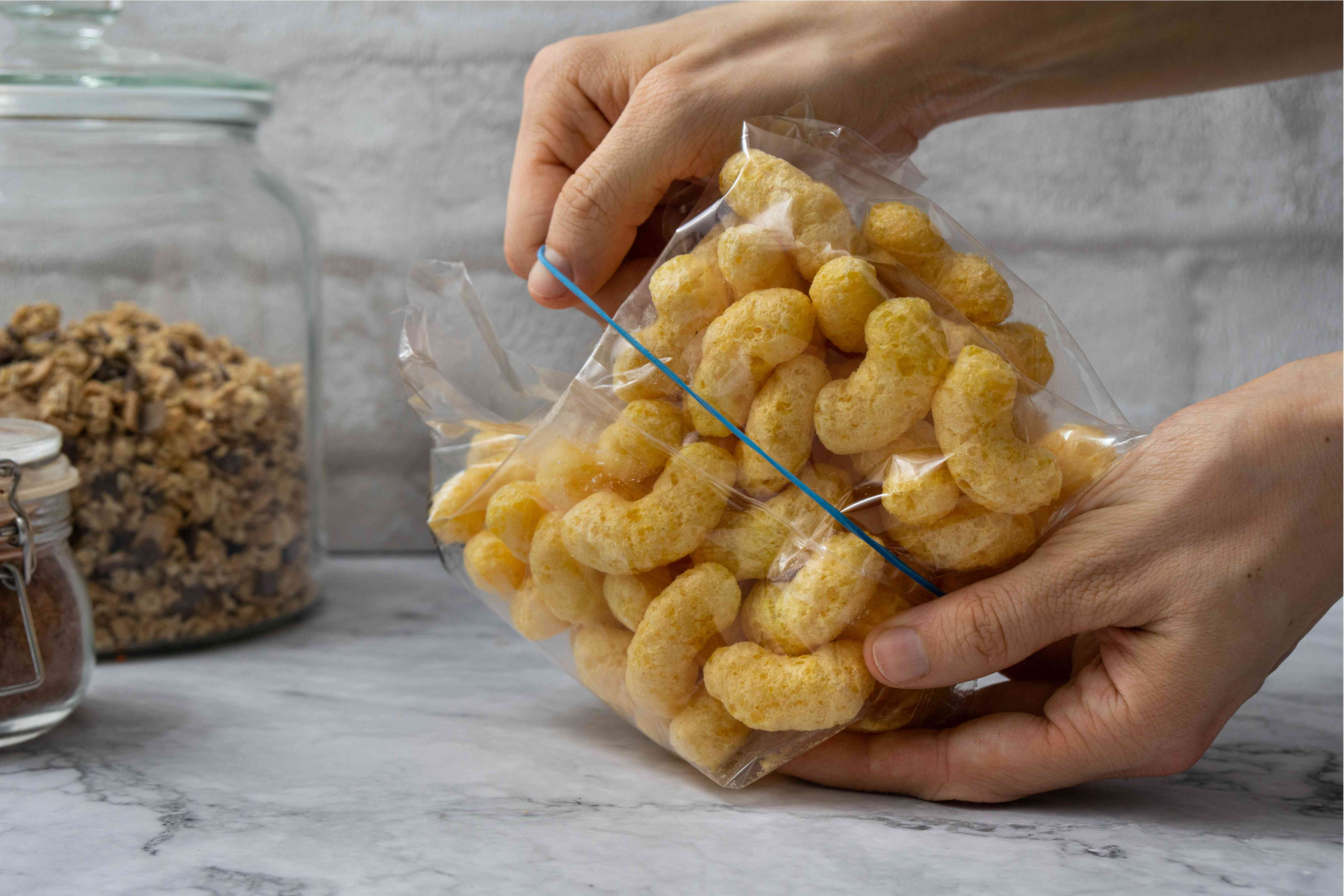 hands seal bag of puffs with rubber band