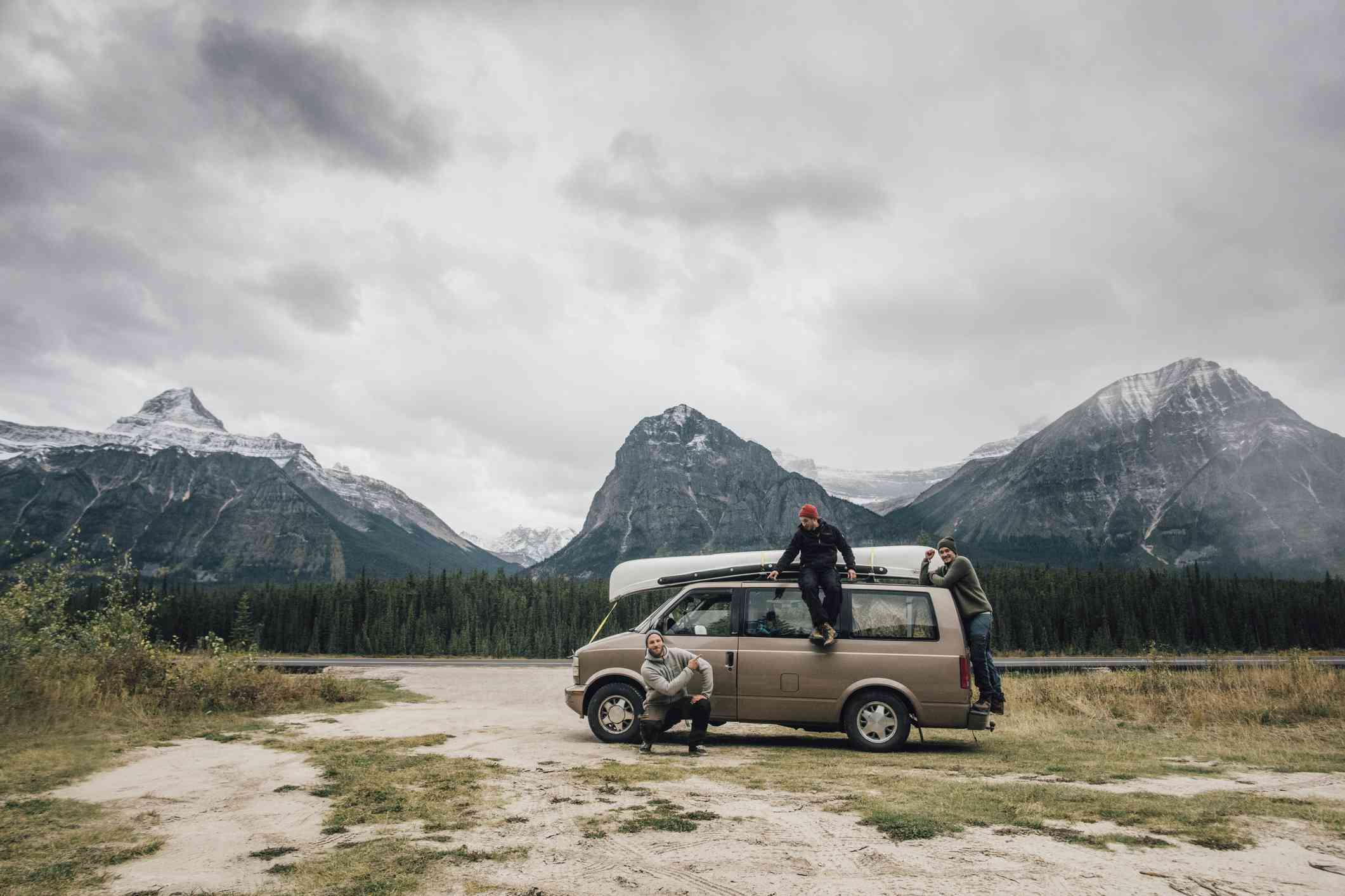 Three people with a van in the mountains, Canada