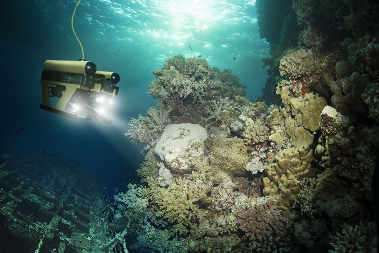 A robot exploring an underwater reef with headlights. A cord hangs from the robot.