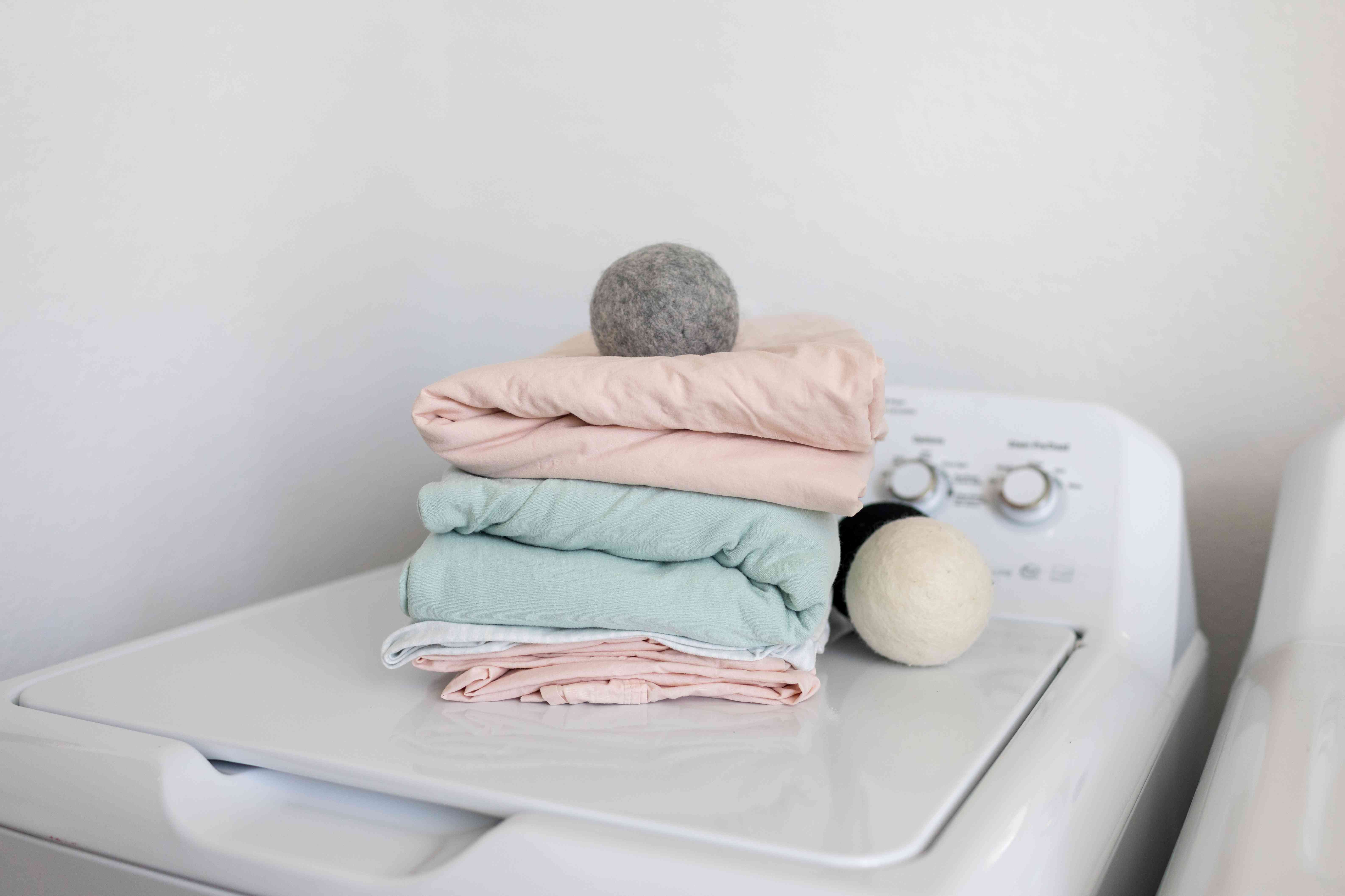 stack of folded bed sheets and wool dryer balls on top of washing machine