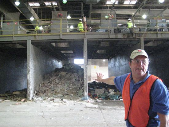 A man wearing protective gear gesturing towards garbage in a waste facility.