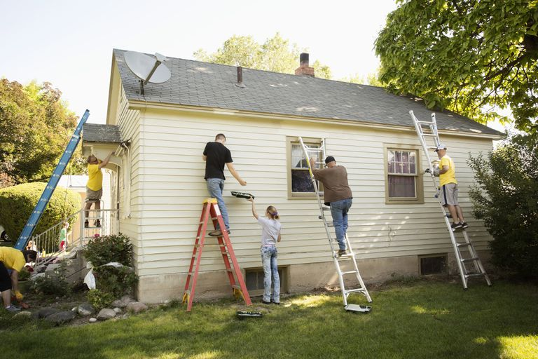People on ladders painting the white siding of a house