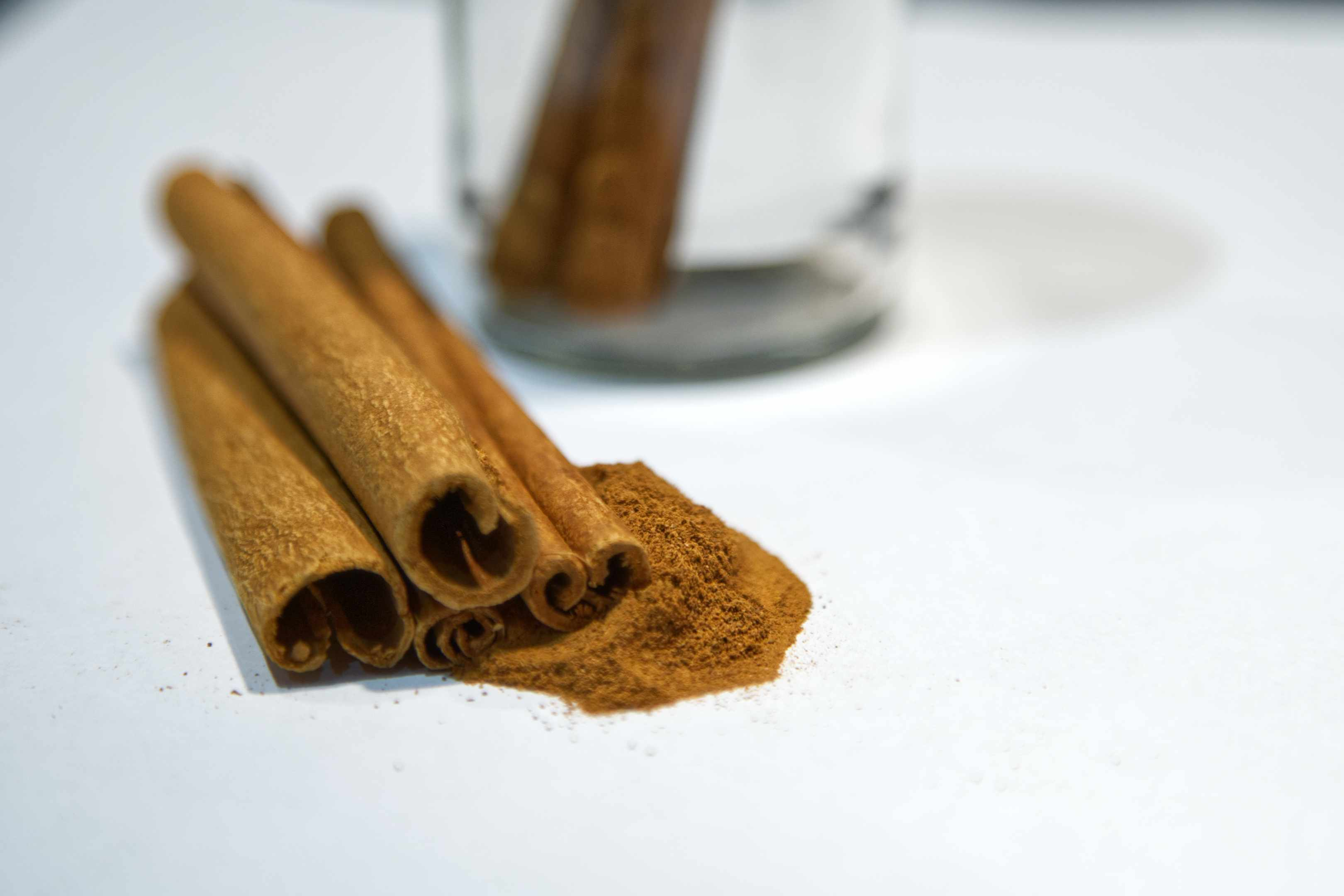 a few cinnamon sticks on white table with more in glass jar in background