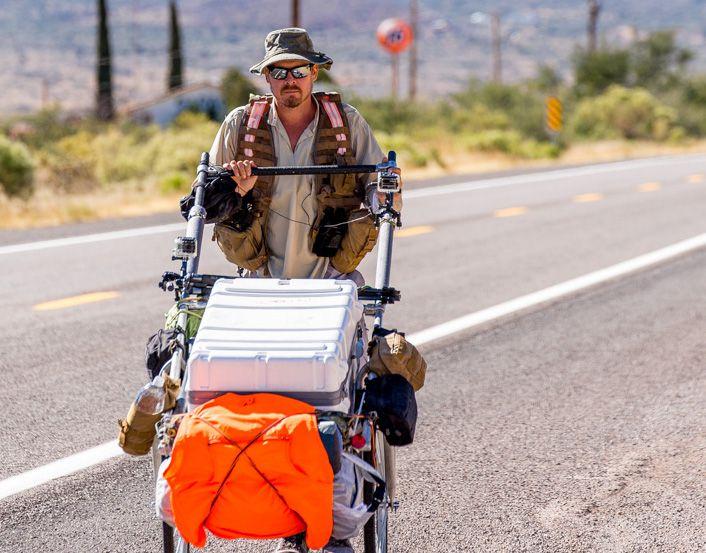 A British man walks along an empty road in full sun pushing a cart.