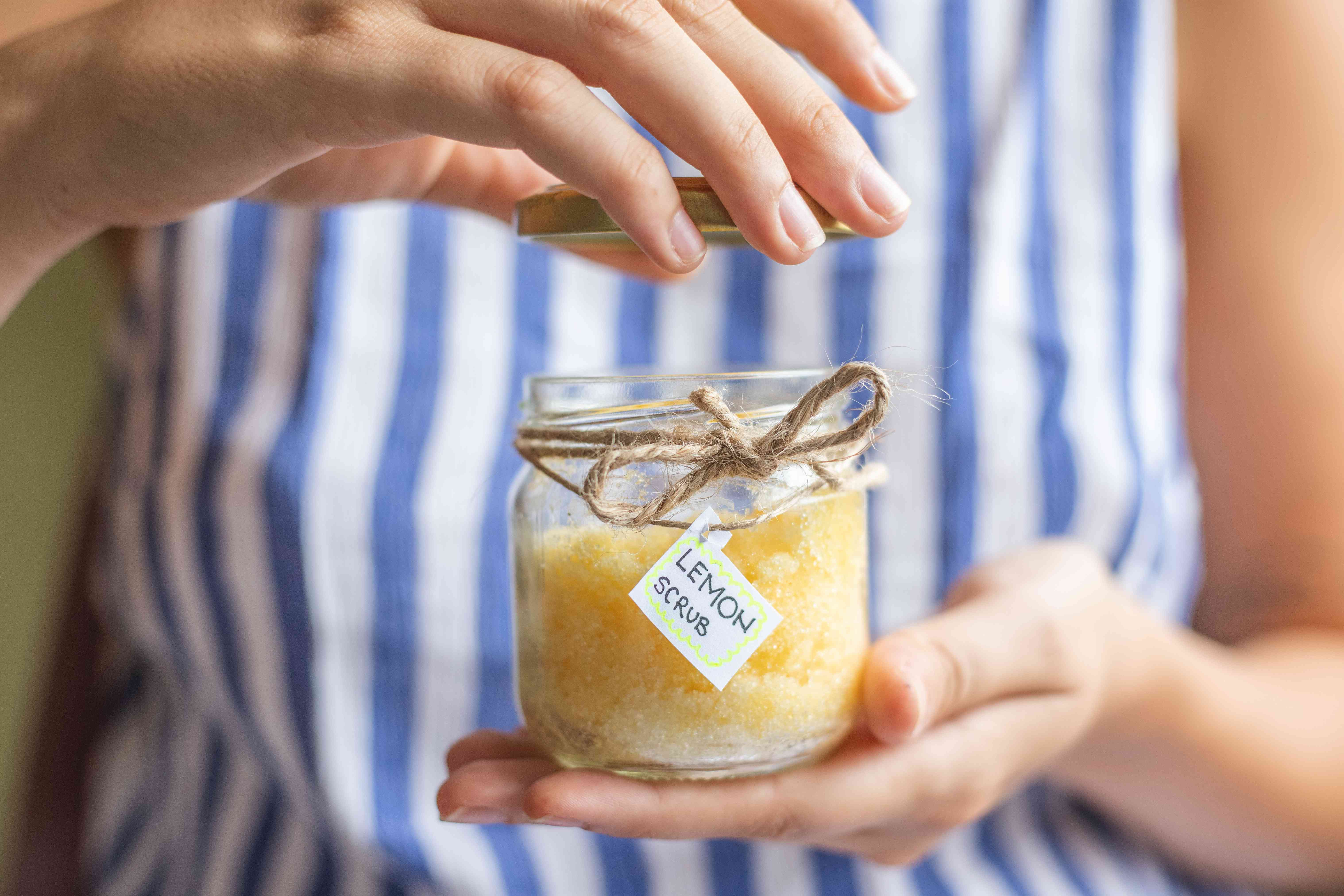 woman in striped top takes off lid of lemon salt scrub in glass container