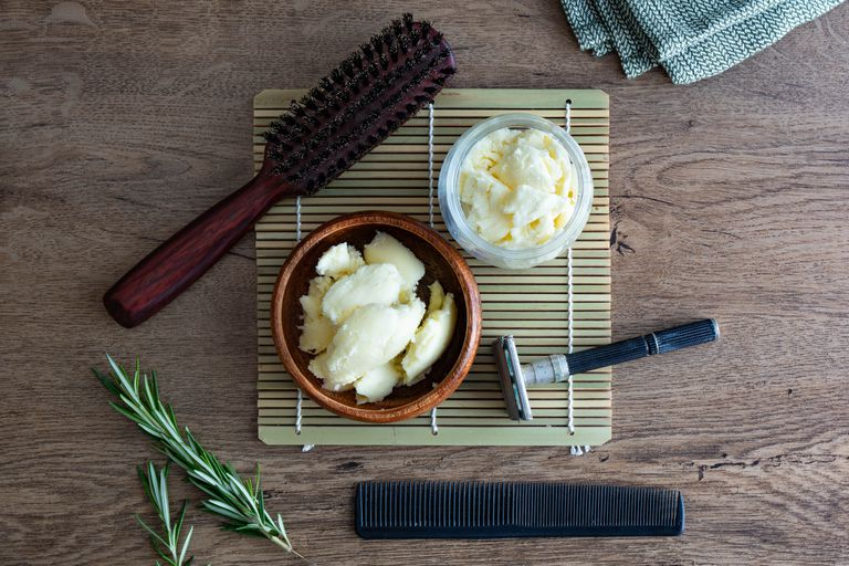 flat lay of raw shea butter in bowls with grooming and hair tools on laminate wood table