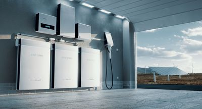 Garage with energy storage batteries and electric vehicle charger, with solar panels in the background.