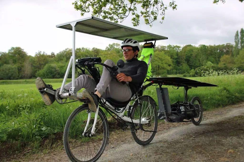 Man riding a recumbent bike towing a trailer