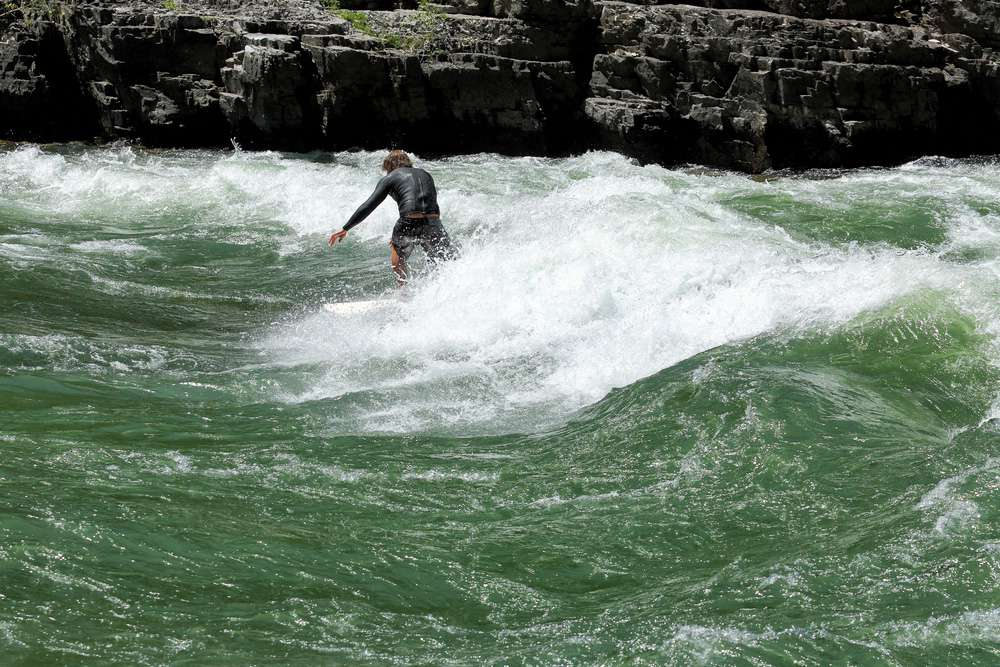 A person surfing on the white water waves of rapids on the Snake River near large rocks