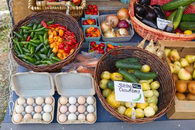 bright vegetables for sell at outdoor farmer market including cucumbers and eggs