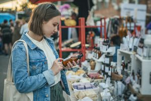 A young white woman reads ingredients on skincare at an outdoor market.
