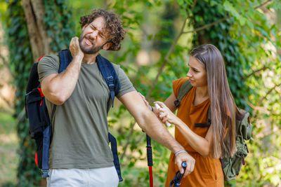 Woman spraying man with bug bites