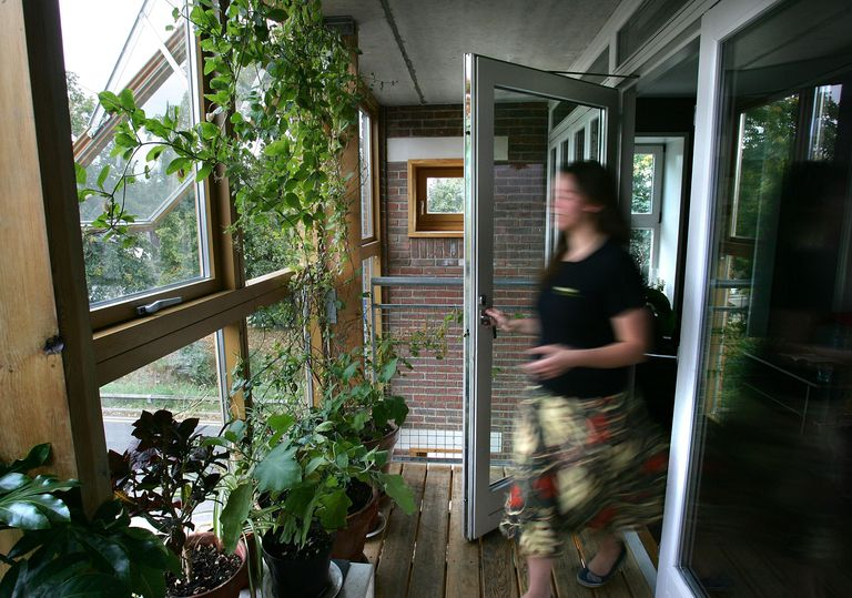 A woman walking around in a zero carbon home with large windows.