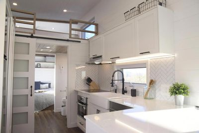 White cupboards and countertops in tiny home kitchen