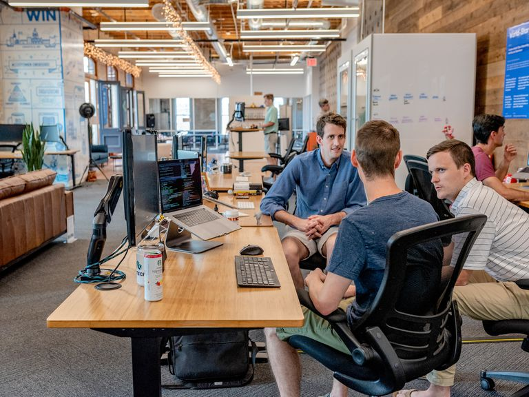 Bright, modern coworking space and three men having a conversation next to a computer station