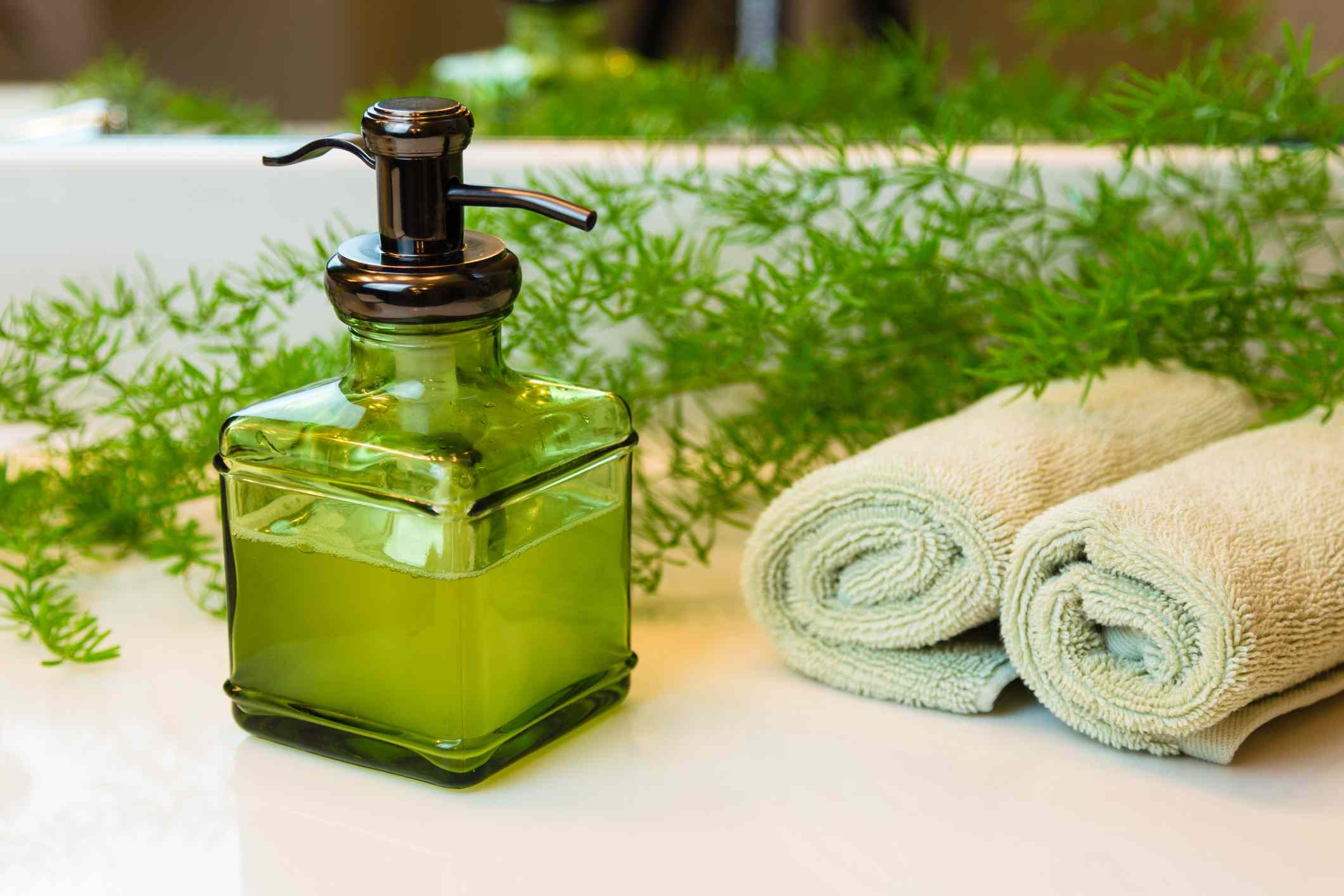 Pump green glass bottle with liquid castile soap. Rolled green towels in a spa setting. Green plant decor in background. Bathroom white countertop