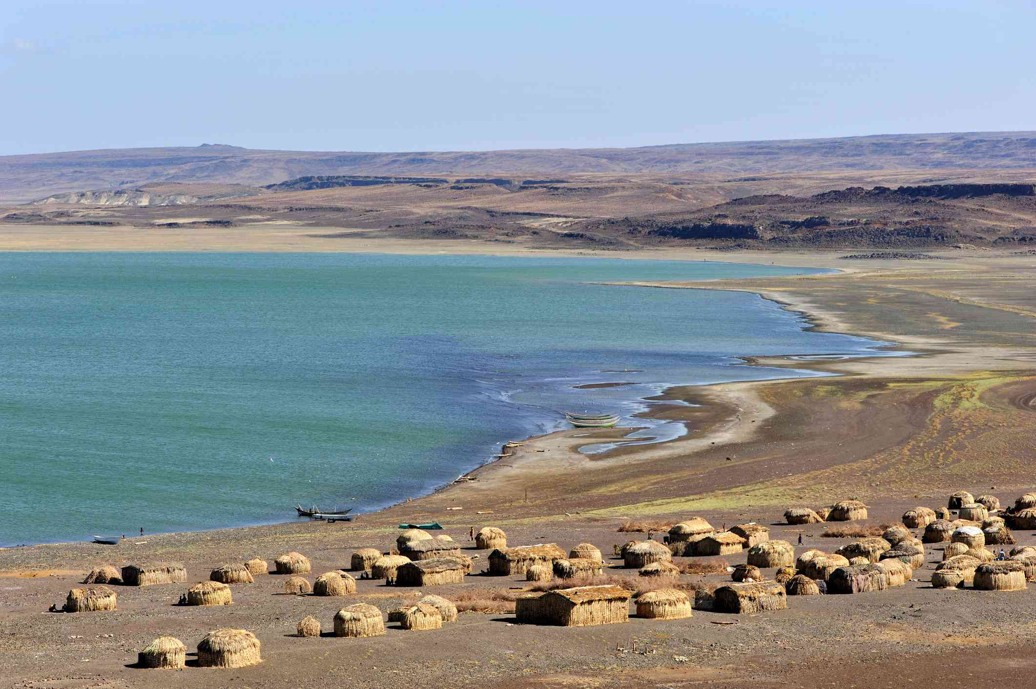 Tan colored African huts in the foreground along the blue-green waters of Lake Turkana under a clear, blue sky