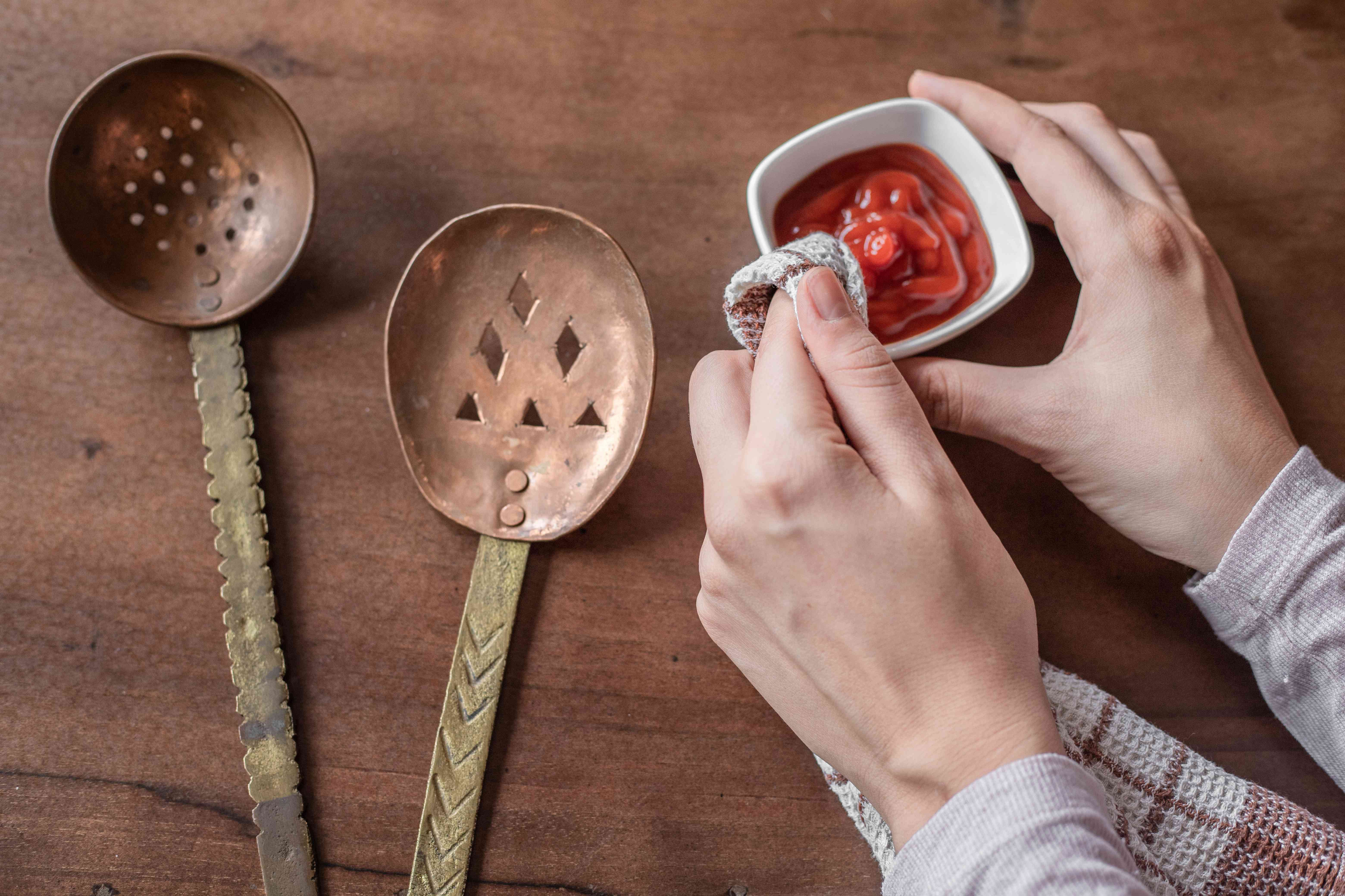 hands clean copper spoons with small bowl of ketchup