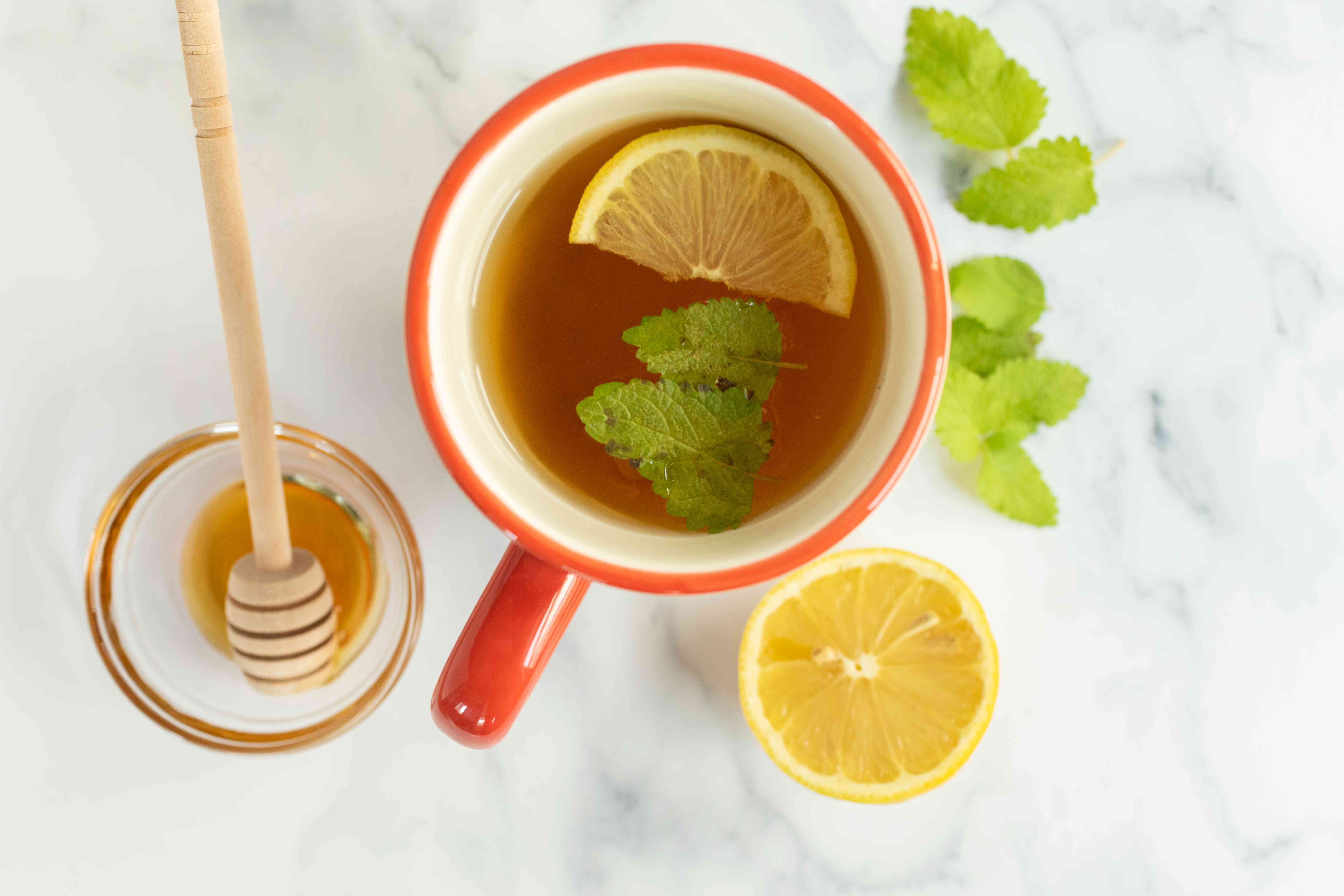 homemade lemon balm tea with honey and fresh leaves steeping in coffee cup