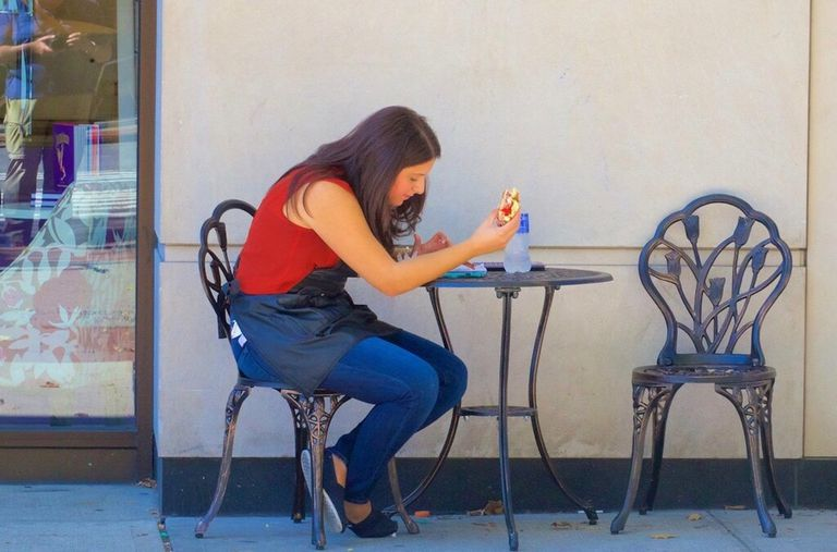 Woman eating alone at outdoor cafe table