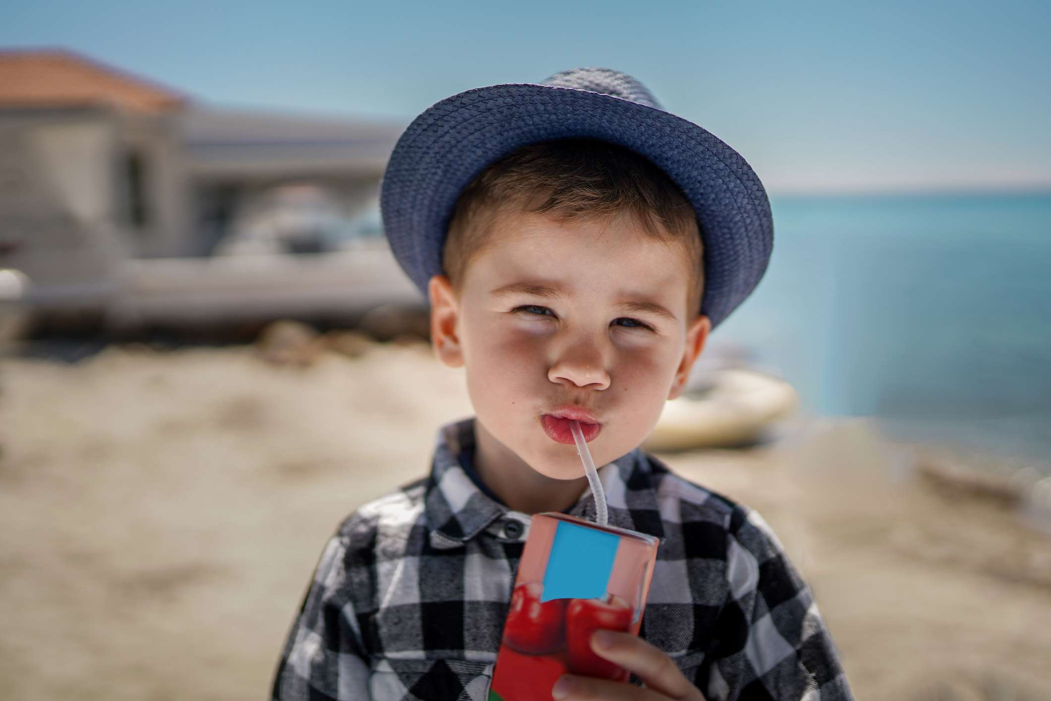 A child at the beach with a juice box.