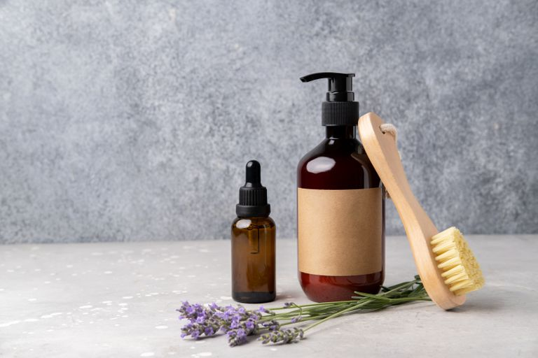 Natural cosmetics with lavender for skincare, body and hair care. Composition with bottles cleansing moisturizer and brush for skin cleansing and massage.