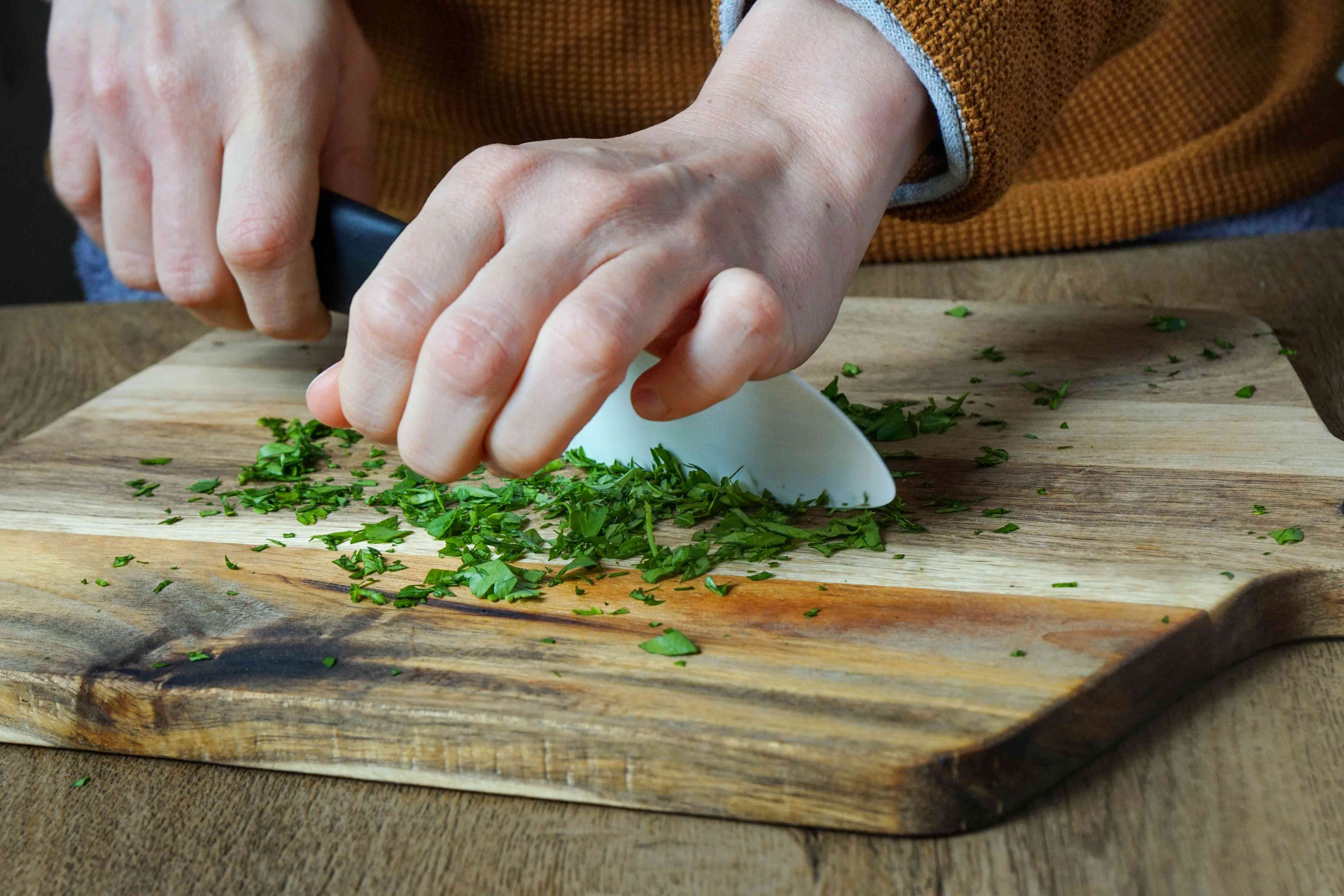 hands chop fresh parsley with white ceramic knife on wooden board