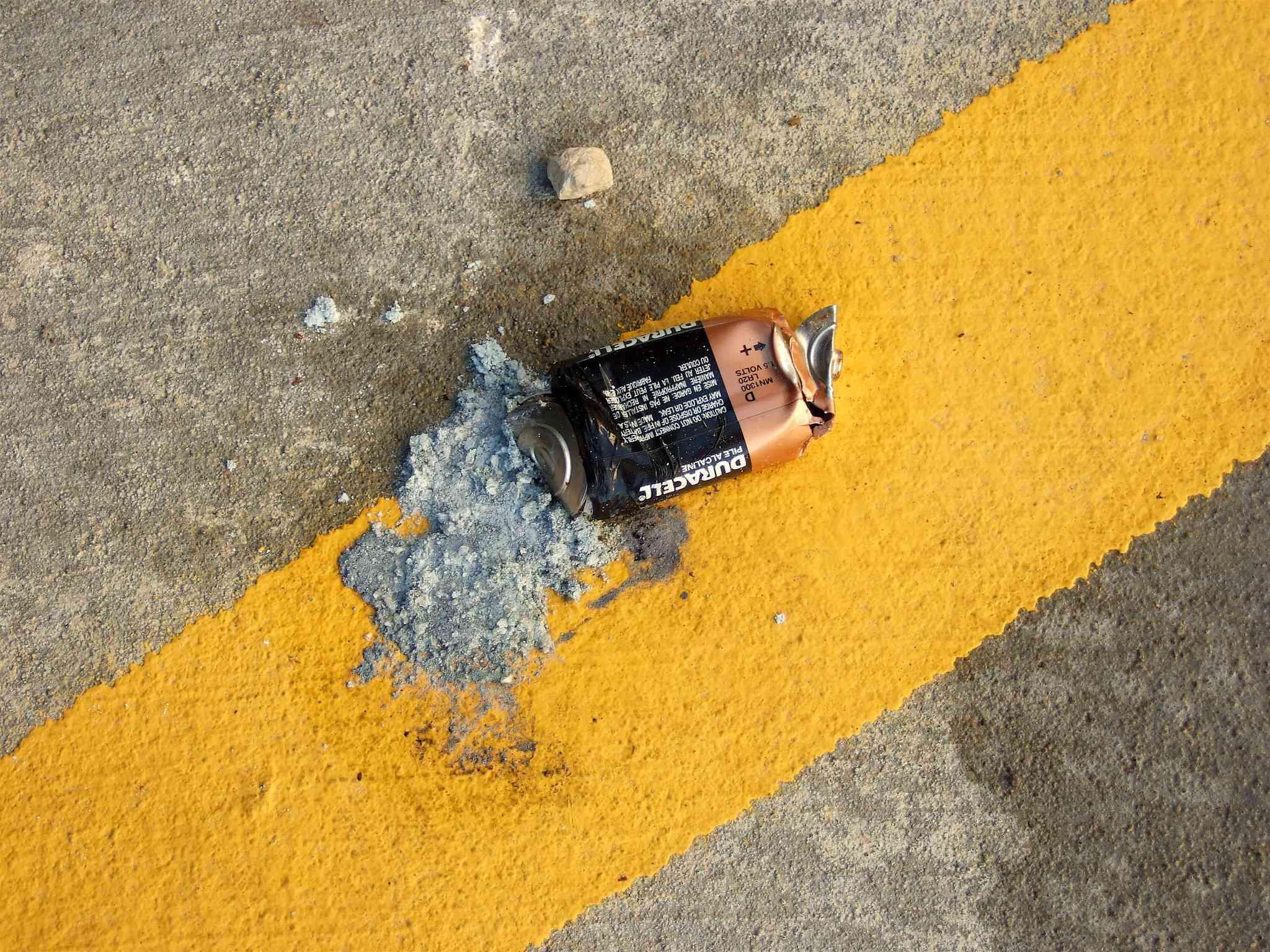 a smushed battery split open on ground