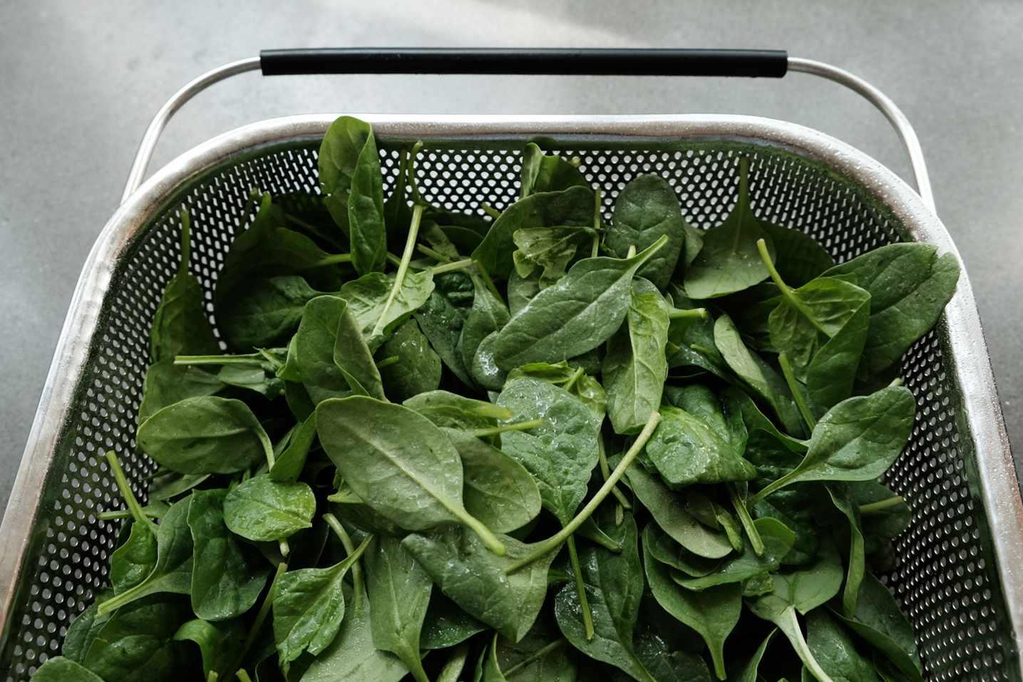 wet spinach in metal colander