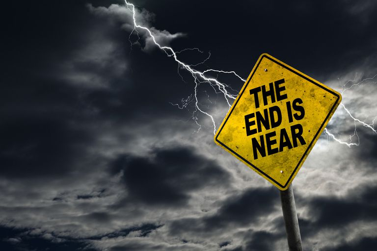 """Sign saying """"the end is near"""" against a dark, stormy sky"""