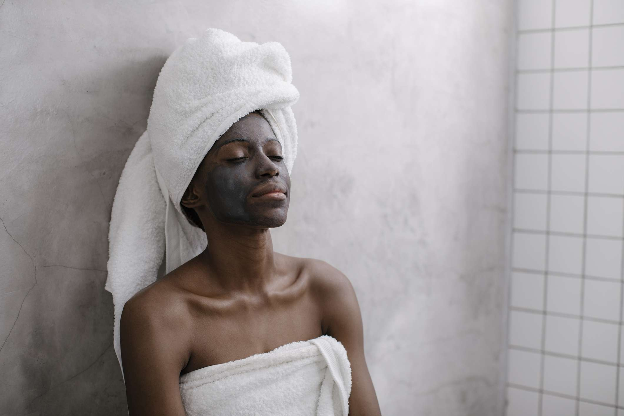 A black woman wearing a charcoal facial mask in the shower.