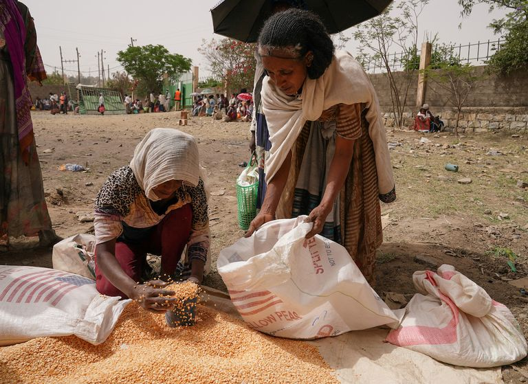 An aid worker distributes measured portions of yellow lentils to residents of Geha subcity at an aid operation run by USAID, Catholic Relief Services and the Relief Society of Tigray on June 16, 2021 in Mekele, Ethiopia.