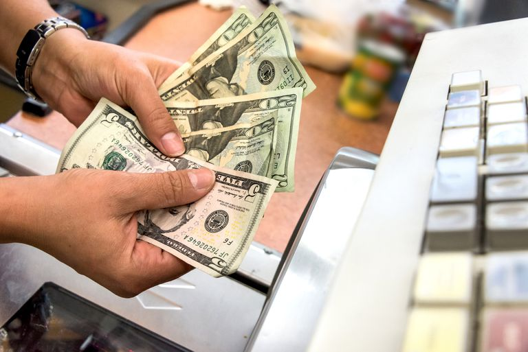 cashier holding four twenty dollar bills and one five dollar bill in front of a cash register