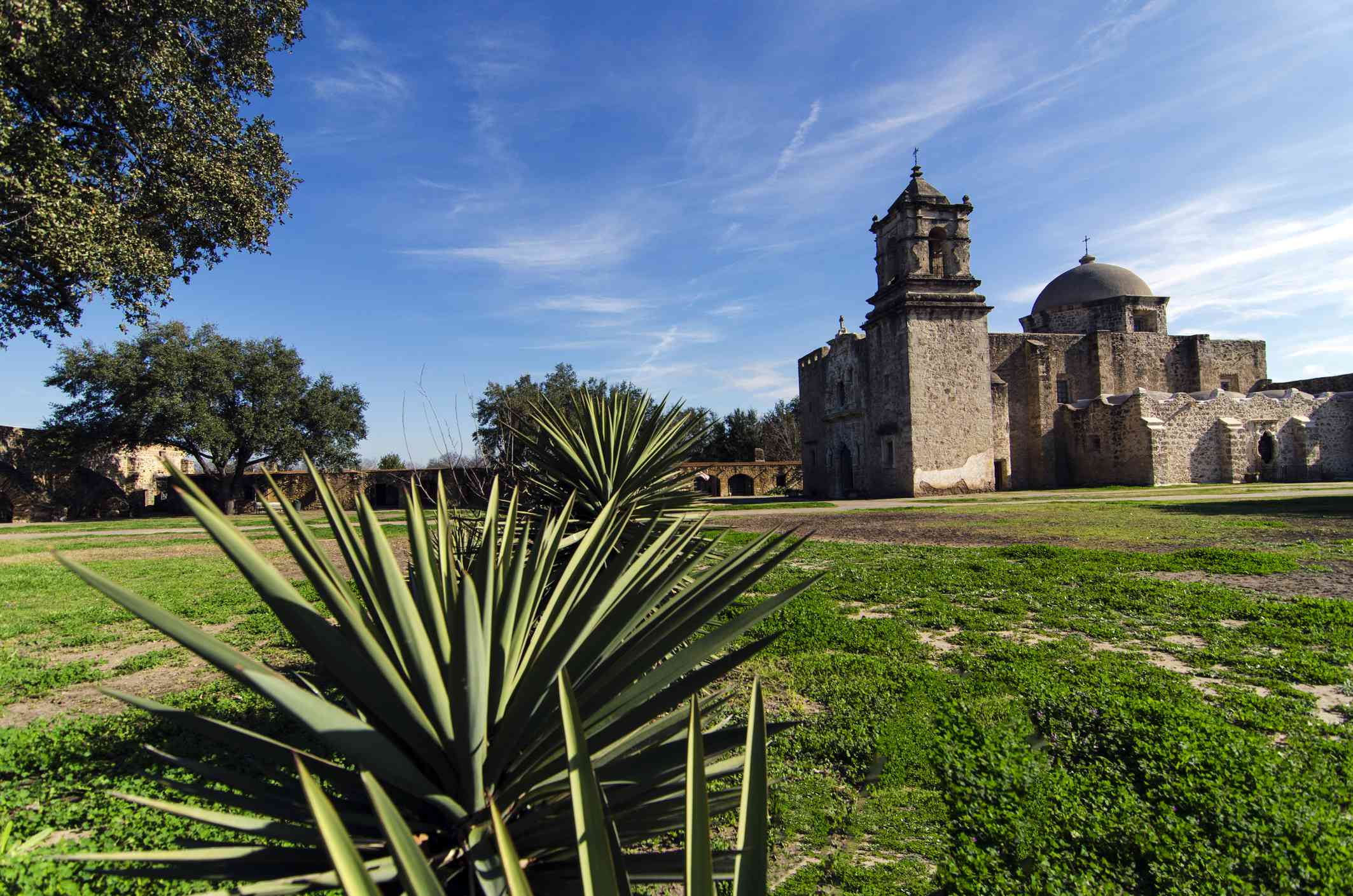 Mission San Jose y San Miguel de Aguayo in the distance below a blue sky with light, white clouds with green grass and low plants in the foreground