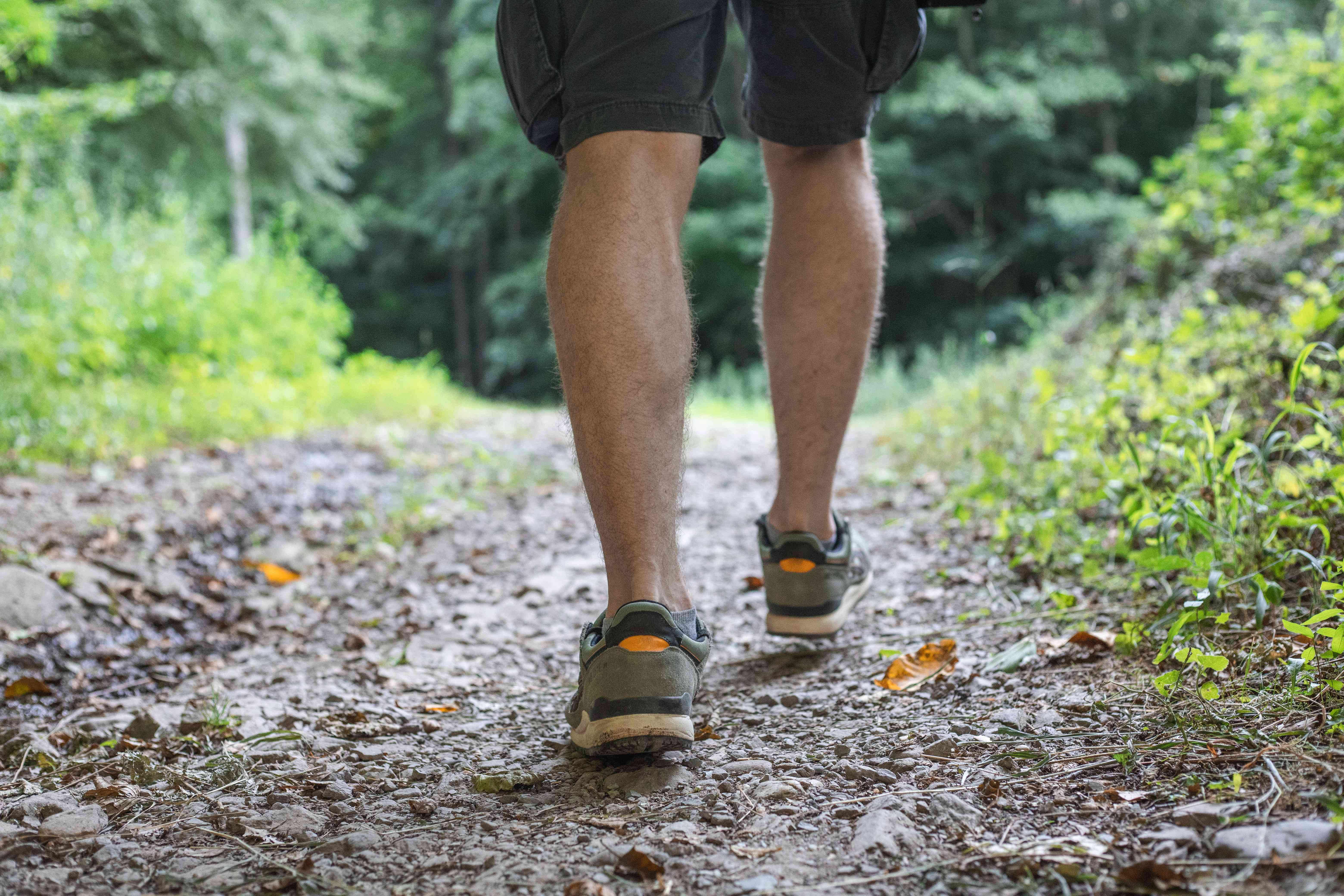 guy in running shoes and shorts stays on hiking trail while heading into woods