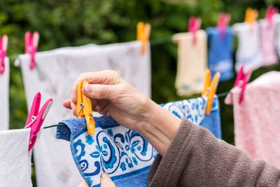 Old woman hanging laundry outdoors