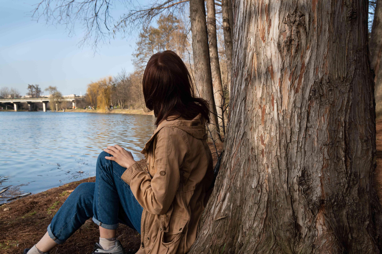 woman sits under large tree near body of water in winter season