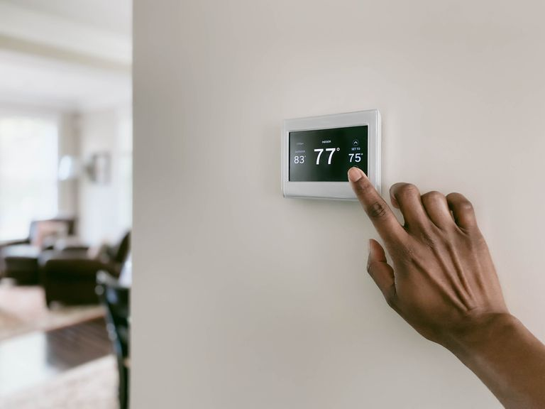 A black hand touching a thermostat on a white wall.