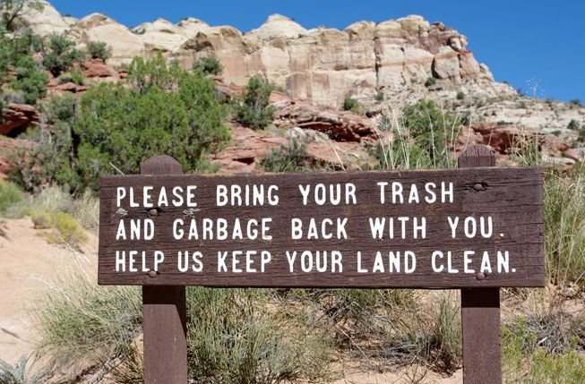 A sign at the start of a national park trail encourages people to collect their own trash