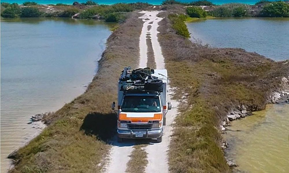 Ambulance driving down sandy path between two bodies of water