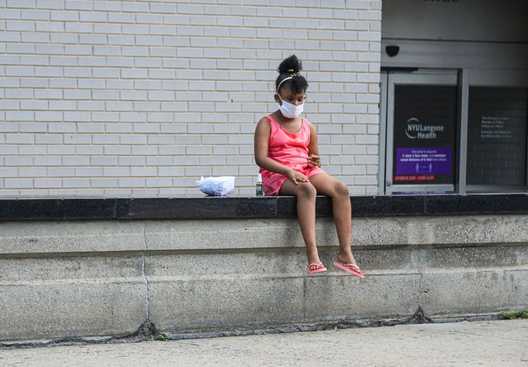 Black girl with mask sitting alone outside a health center