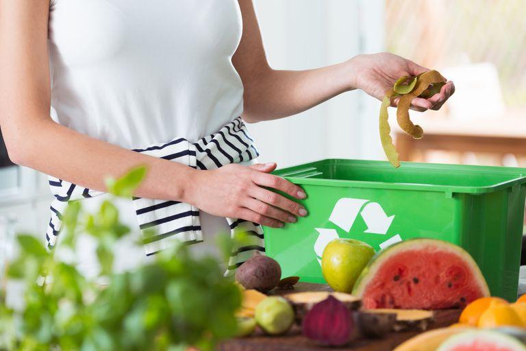Woman composting organic kitchen waste