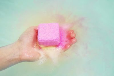 A white hand holding a pink and yellow bath bomb in water.