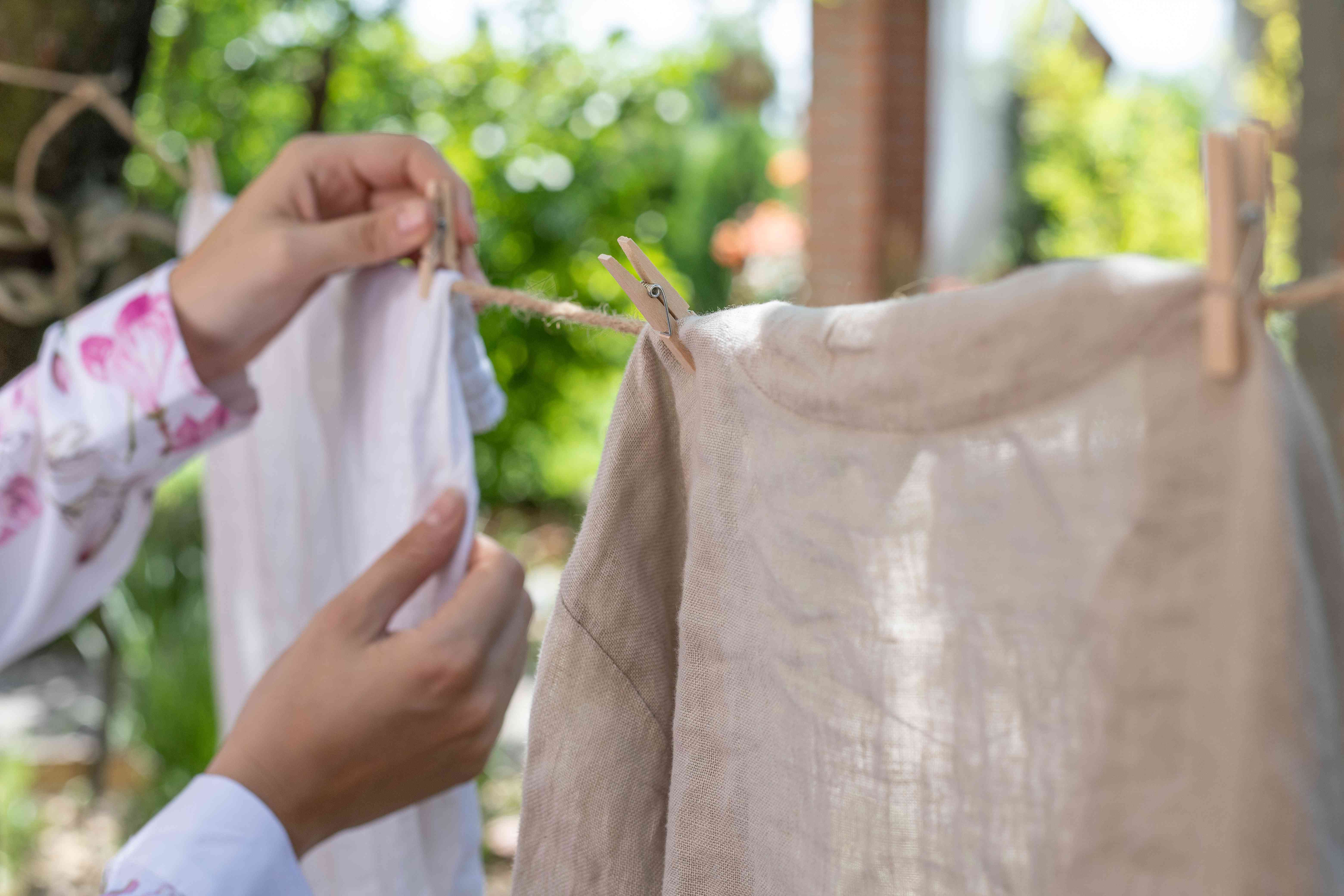person hangs up white cotton and tan linen clothing on clothesline outside