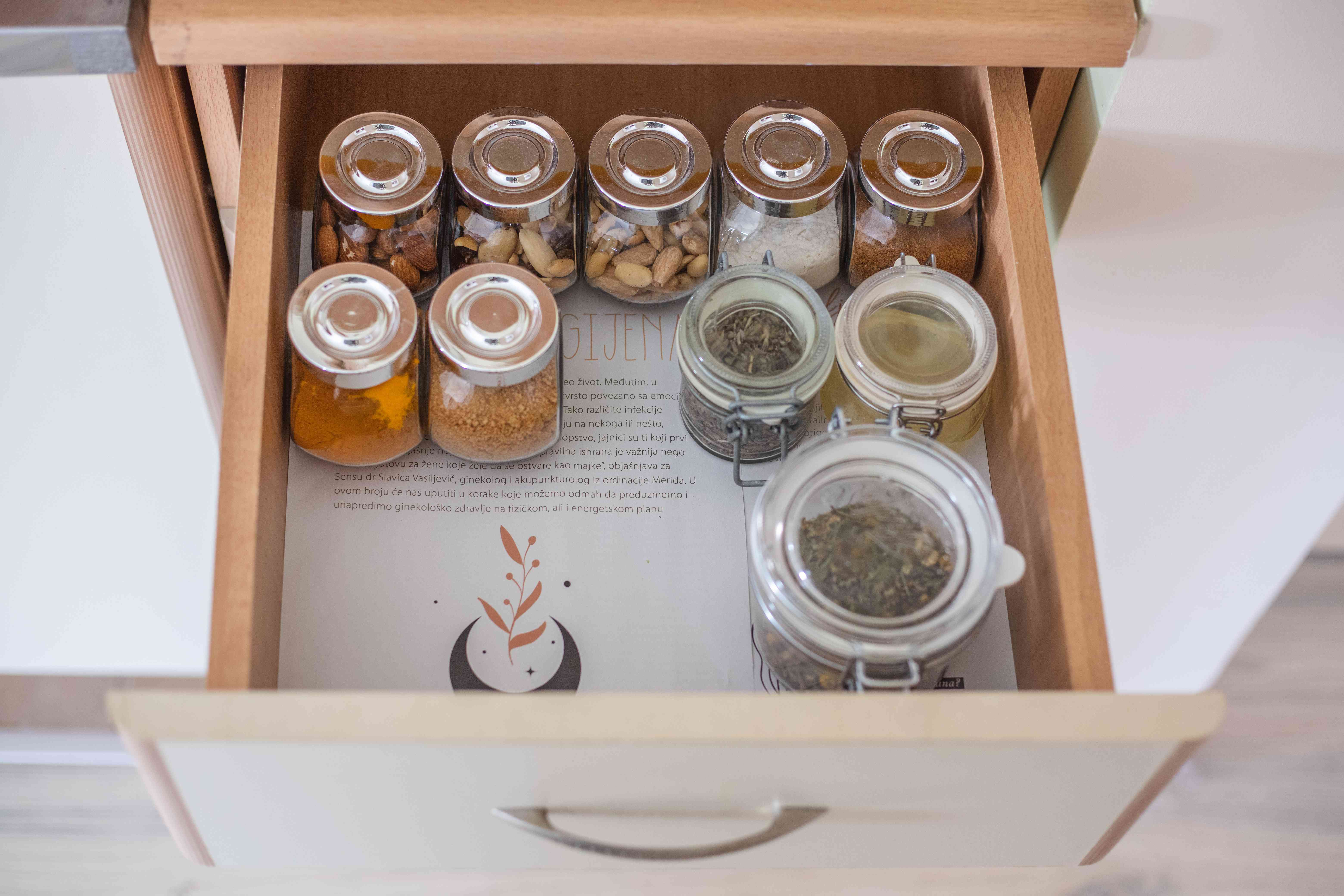 kitchen spice drawer pulled out to show magazine paper used as lining