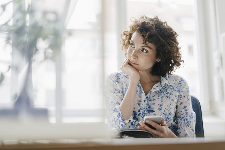 Businesswoman in office with smartphone looking pensive