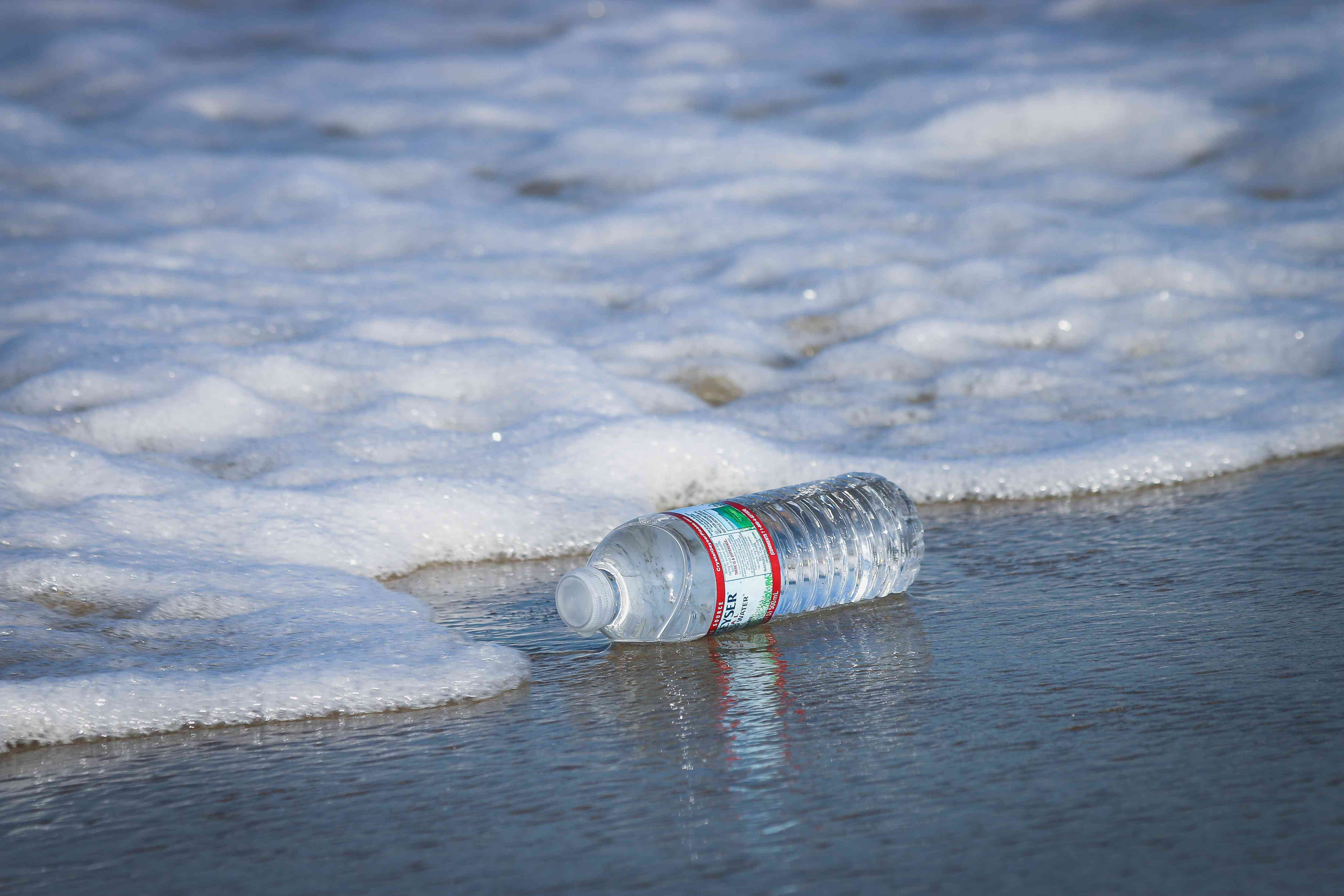 Plastic water bottle next to the surf on a beach
